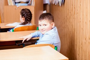 cute boy is sitting on the lesson