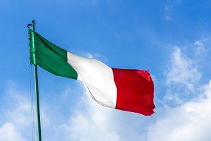 Waving Italian flag against blue sky