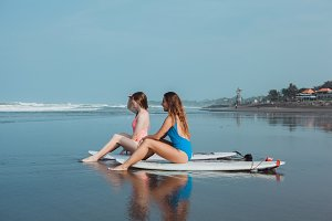 Two surfing girls posing on ocean