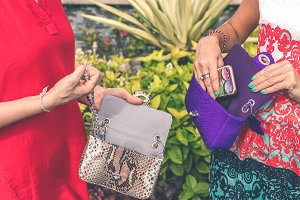 Woman hands with luxury handmade snakeskin leather handbag. Python snake fashionable handbag. Outdoors, Bali island.