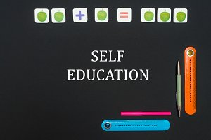 Black art table with stationery supplies with text self education on black board