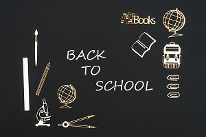 School supplies placed on black background with text back to school