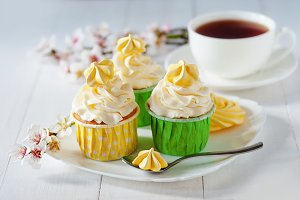 Beautiful flowers on wooden table with white vanilla capcake with meringues and cup of coffee,