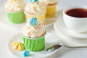 A beautiful bright ladies tea party with cup of tea cupcake with meringues