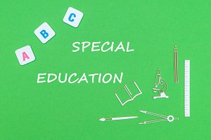 text special education, from above wooden minitures school supplies and abc letters on green background
