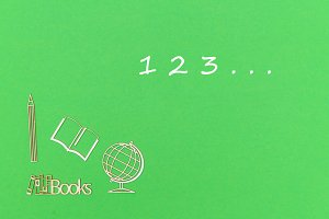 text 123, school supplies wooden miniatures on green background