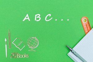 text abc, school supplies wooden miniatures, notebook on green background