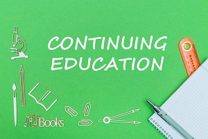text continuing education, school supplies wooden miniatures, notebook with ruler, pen on green backboard