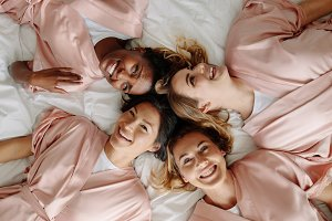 Bride with bridesmaids lying on bed