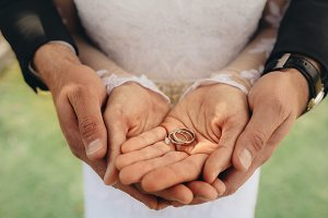 Bride and groom holding wedding ring