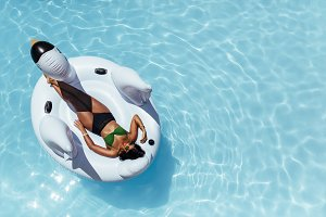 Woman relaxing on inflatable swan