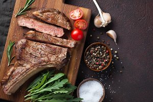 Grilled cowboy beef steak, herbs and spices on a dark stone background. Top view with copy space for your text