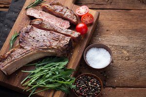 Grilled cowboy beef steak, herbs and spices on a rustic wooden background. Top view with copy space for your text