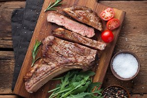 Grilled cowboy beef steak, herbs and spices on a rustic wooden background. Top view