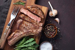 Grilled cowboy beef steak, herbs and spices on a dark stone background. Top view