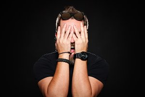 A bearded man holds his hands behind his face and screams in studio on a black background
