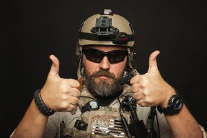 Brutal man in military desert uniform and body armor shows two fingers up on black background in Studio. The bearded player in the airsoft safety glasses or goggles and active headphones