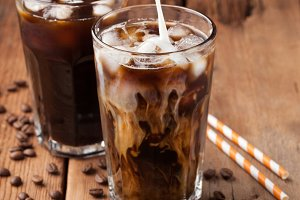 Ice coffee in a tall glass with cream poured over and coffee beans on a old rustic wooden table. Cold summer drink on a dark wooden background