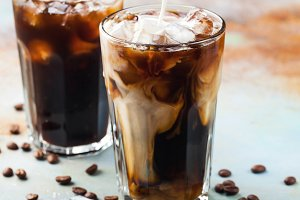 Ice coffee in a tall glass with cream poured over and coffee beans. Cold summer drink on a blue rusty background