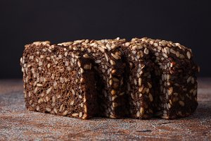 Fresh black bread with sunflower seeds on an old rusty table