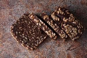Fresh black bread with sunflower seeds on an old rusty table. Top view