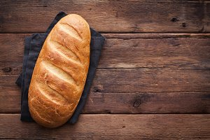 Fresh bread on wooden table. Top view with space for your text