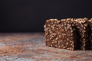 Fresh black bread with sunflower seeds on an old rusty table. With copy space