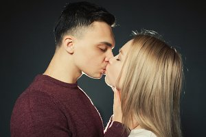 Portrait of a beautiful young couple in love posing at studio over dark background. Guy and girl kissing close up
