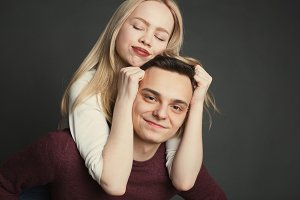 Portrait of a beautiful young couple in love posing at studio over dark background. Girl sitting on the shoulders of a young man and holds him by the hair
