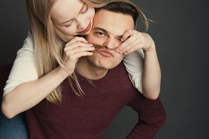 Portrait of a beautiful young couple in love posing at studio over dark background. Happy couple making false moustache from hair and smiling at camera