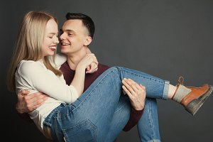 Portrait of a beautiful young couple in love posing at studio over dark background. The guy holds his beloved in his arms and smiles