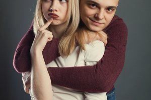 Portrait of a beautiful young couple in love posing at studio over dark background