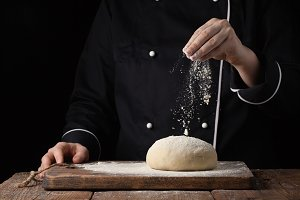 Chef hands pouring flour powder on raw dough using sieve on a black background, Cooking process