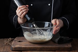 Female chef stirring his batter with a whisk on a black background