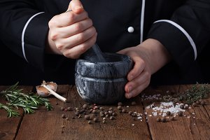 Woman chef pounding spices and herbs in mortar for food cooking on a black background