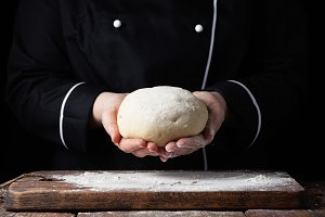 Female chef holding yeast dough in her hands on black background