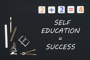 School supplies placed on black background with text self education success