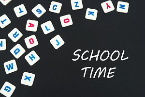 english colored square letters scattered on black background with text school time