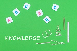 text knowlwdge, from above wooden minitures school supplies and abc letters on green background