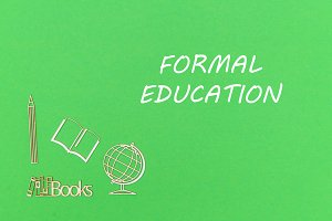 text formal education, school supplies wooden miniatures on green background