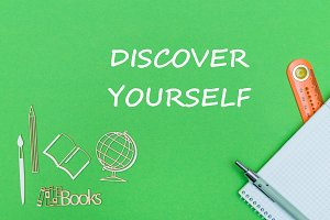 text discover yourself, school supplies wooden miniatures, notebook on green background