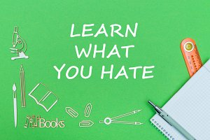text learn what you hate, school supplies wooden miniatures, notebook with ruler, pen on green backboard