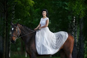 beautiful girl in dress sitting on horse