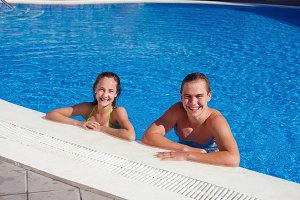 boy and girl having fun in swimming pool
