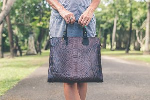 Woman hand with luxury snakeskin handbag outdoors. Tropical fashion exotic concept.
