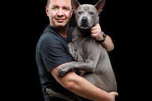 man holding thai ridgeback dog