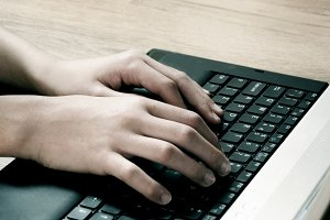 Boy hands typing on a laptop