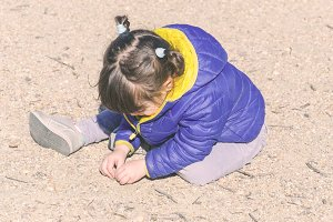 girl with braids playing in the sand