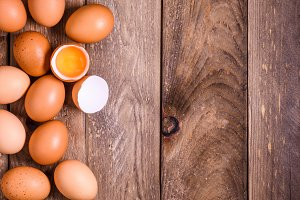 Brown eggs on wooden table with one