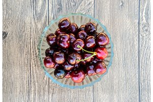 Berries of a sweet cherry in a glass bowl on a wooden background. Ripe red sweet cherry